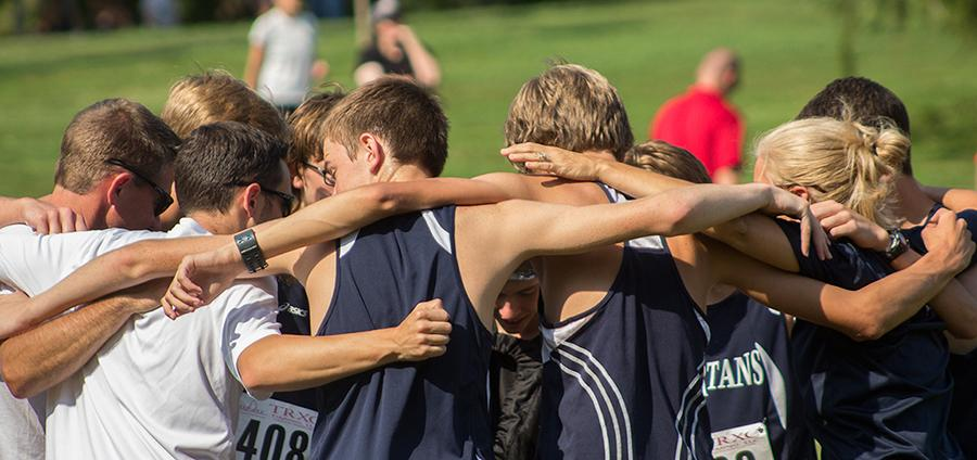 The boy's cross country team huddles up before their meet on Aug 29. They were among the top teams in the 'outstanding award' category with an average GPA of 3.92.