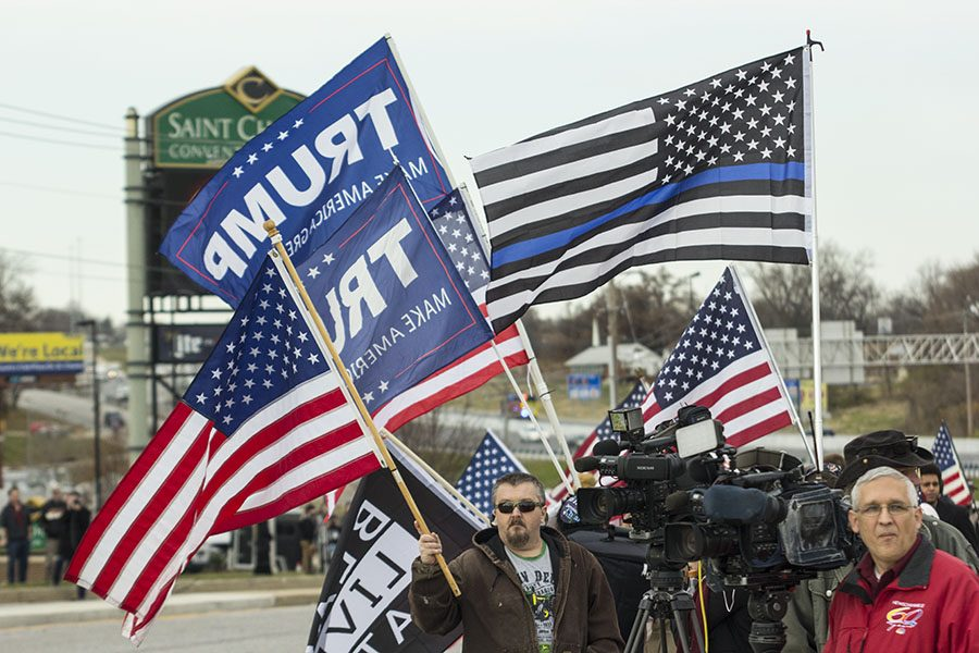 Protesters+outside+the+St.+Charles+Convention+Center+wave+Trump+flags+while+awaiting+his+arrival.+President+Trump+traveled+to+St.+Charles+to+speak+about+tax+cuts.+